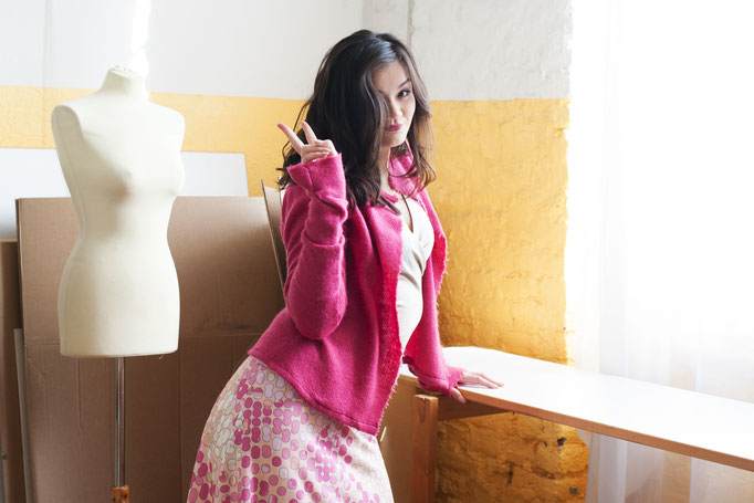 Melanie trägt  eine Strickjacke aus Merinowolle, Auflage 3 Stück, 229€; einen ausgestellten Tupfenrock mit Spitzenbund, Auflage 3 Stück, 159€ und ein Wickeltop aus Baumwolle, 129€