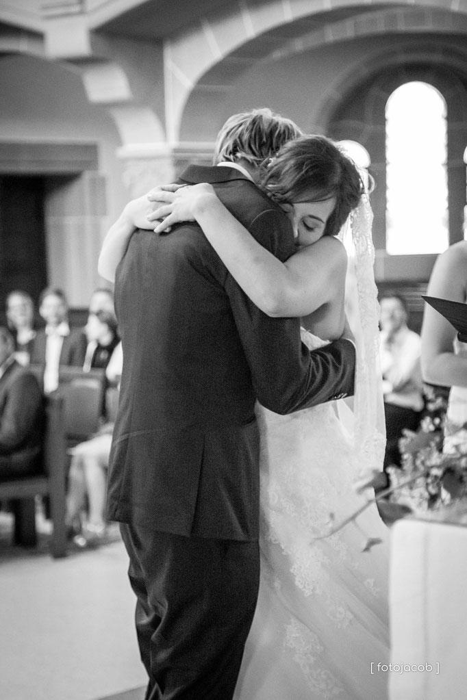 brautpaar umarmt sich innig vor dem altar in der evangelischen peterskirche in weinheim