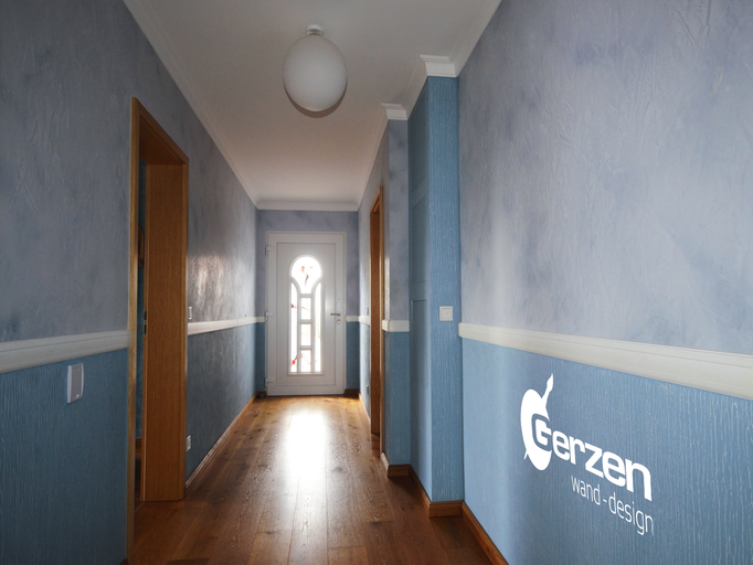 Flurgestaltung in Hellblau mit Patina-Effekten und plastischem Modellierputz
