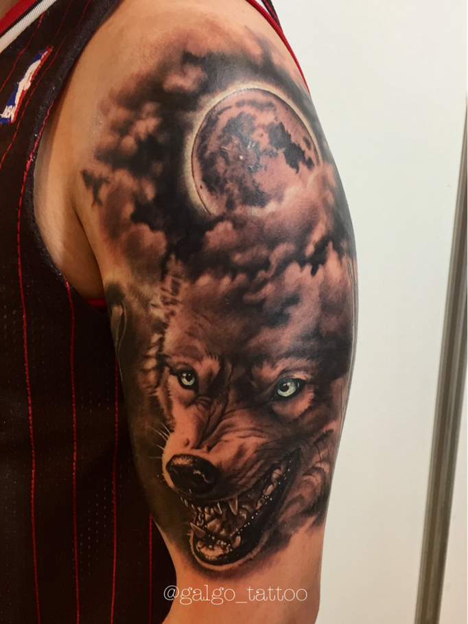Realistic tattoo of a wolf with a full moon on the background.