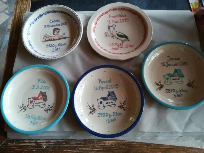 Geburtenteller (von links nach rechts): Motiv Wiege in mint; Motiv Baby mit Wellenrand; Motiv Wiege in blau; Motiv Storch in koralle; Motiv Wiege in mint