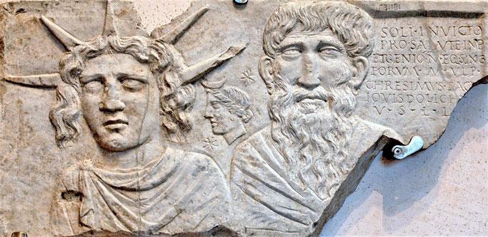 Plaque votive consacrée au Soleil Invaincu représentant le dieu Soleil couronné de rayons solaires, la déesse de la Lune portant un croissant sur ses cheveux et un vieil homme, peut-être Jupiter Dolichenus.