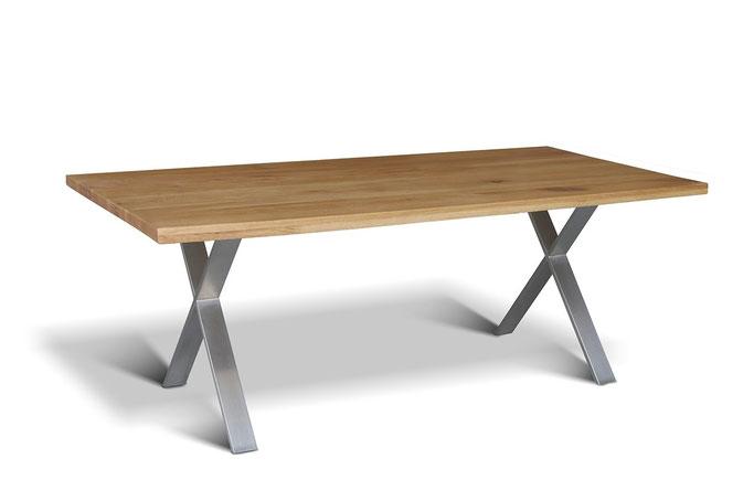 Ein Kreuzgestell Esstisch ais gebürstetem Edelstahl mit einer massiven Eiche Tischplatte
