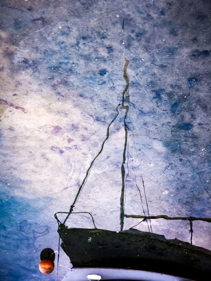 Effleurant le ciel  Le bateau erre et vogue entre  Les nuages du fond