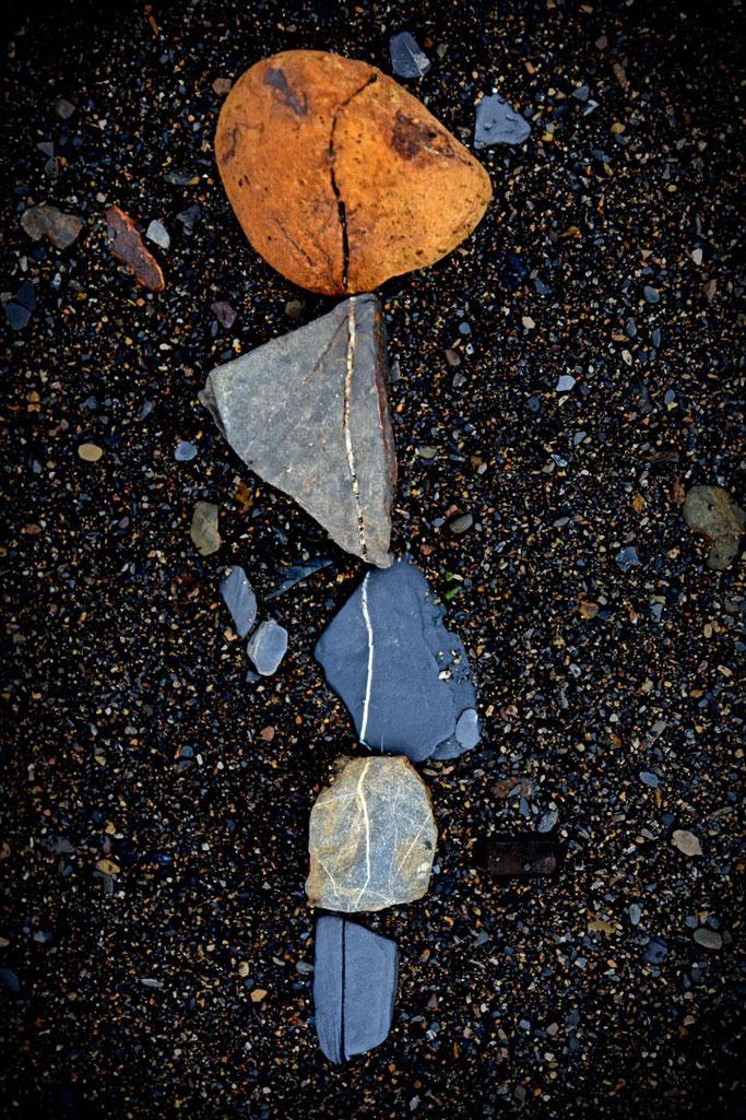 Deux, trois, quatre et cinq  Galets qui font la foire  Sur le sable noir