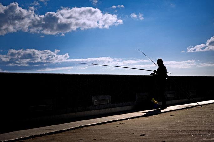 photographe brest plougastel-daoulas bretagne pêcheur pêche à la ligne silhouette portrait passant ciel bleu mer quai ambiance portuaire paysage breton ombre contraste clair obscur