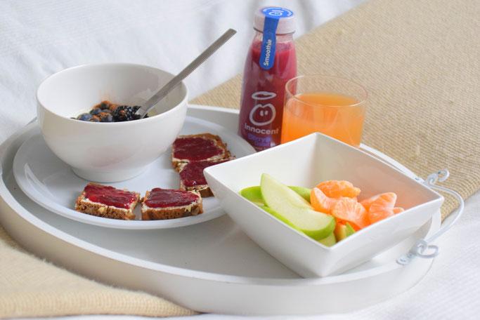 Gemütliches Frühstück im Bett mit Joghurt, Obst, Smoothie, Saft und Marmeladenbrot von Glück Marmelade.