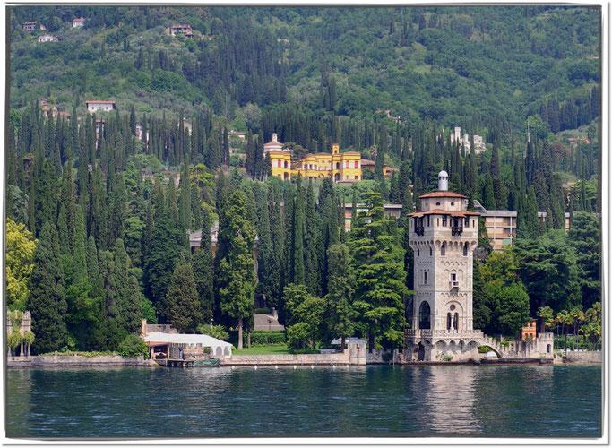 Blick vom Gardasee auf den Leuchtturm von Riviera, im Hintergrund der Vittoriale degli Italiani.
