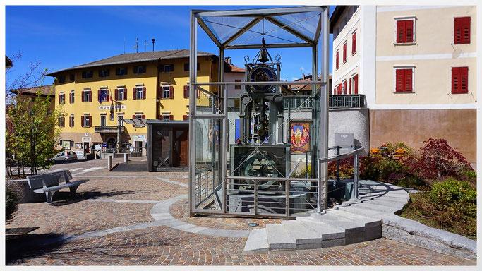 Rathaus von Fondo und auf dem Piazza San Giovanni eine Uhr die mit Wasser angetrieben wird.
