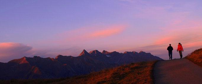 Zwei Spaziergänger in der Region Col des Mosses, mit rotgoldenem Abendhimmel