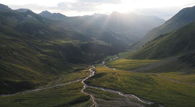 Aussicht von der Hütte in der Abendstimmung nach dem Regen, die Bäche glitzern im Tal von der Sonne.