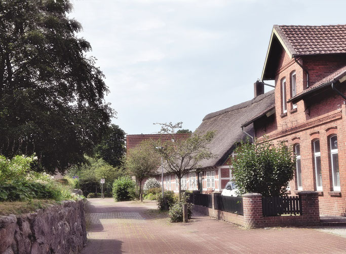 Hinter der Kirche.  Da geht es z.B. zur Heinrich Behnken Schule und auch der Weg zum Arzt Dr. zum Felde kann hier entlang führen.