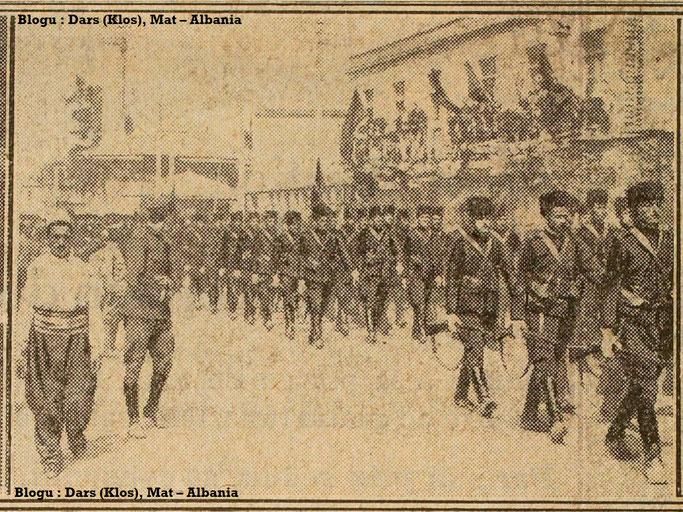 Foto : Parada e ushtarëve para shtëpive të zbukuruara. – Burimi : gallica.bnf.fr / Bibliothèque nationale de France