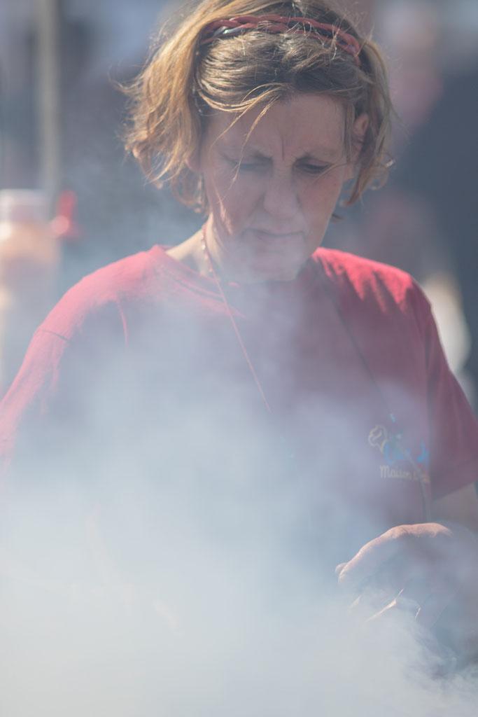 Eine Frau brät Bratwürste auf dem offenen Feuer. Foire de Lessay