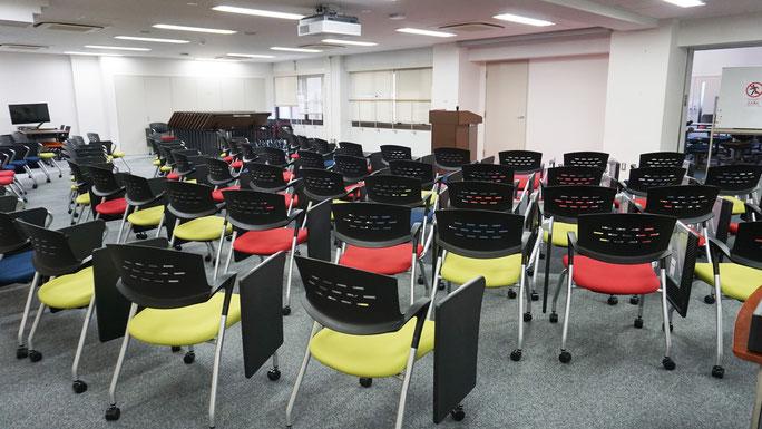 チェアテーブル付きの可動椅子100席、プロジェクタ、講義収録・配信システムが完備。中規模のセミナーやプレゼンテーションに活用できる広々としたスペースである。机と椅子は自由自在に動かすことが可能で、様々な利用シーンに対応できる機能的に充実した空間である。教員のみ予約可能。