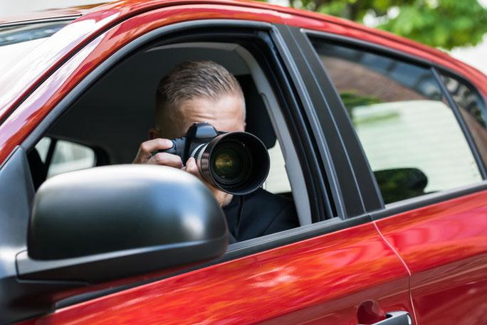 Detektiv mit Kamera bei der Fahrzeugobservation; Mitarbeiterkontrolle Bielefeld, Detektei Bielefeld, Privatdetektiv Bielefeld