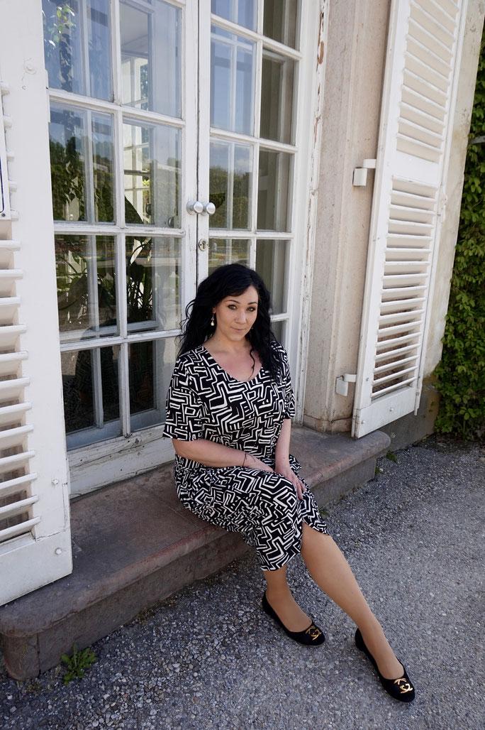 Plus Size Model mit Kleid in schwarz-weiß