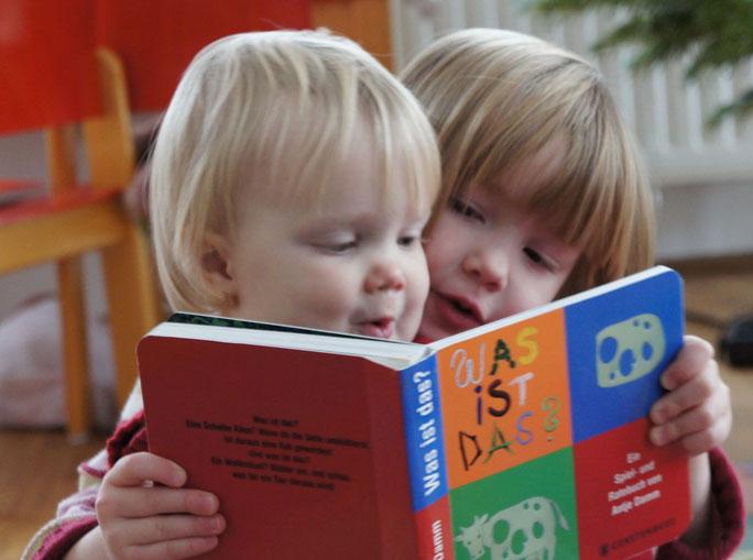 Bild: Kinder lesen gemeinsam ein Buch