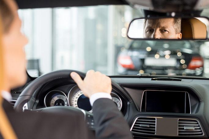 Mann sitzt im Auto und blickt in den Rückspiegel; Detektiv München, Detektei München, Privatdetektiv München