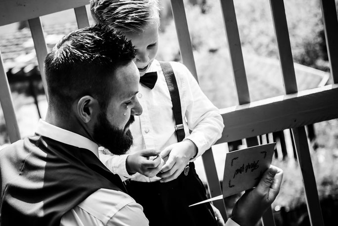 Black and white photo of groom and son on wedding day. They are reading a card. Groom has tear on cheek.