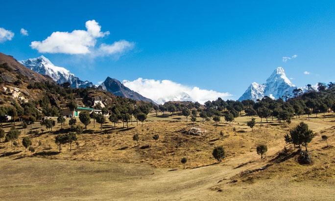 Ein Bild wie aus dem Märchen - rechts hinter dem dunklen Berg, blickt die Spitze des Mount Everest hervor und rechts ist die majestätische Ama Dablam zu sehen.