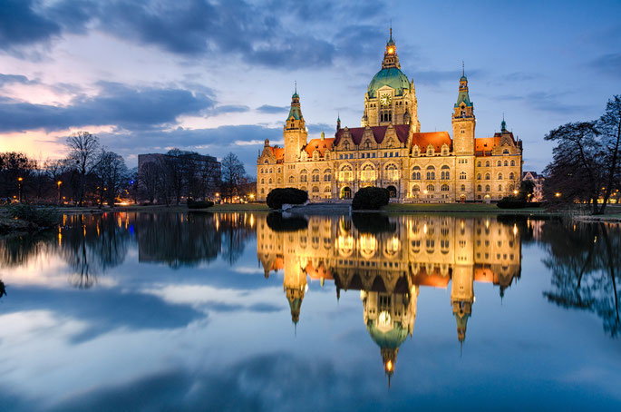 Das Neue Rathaus in der Dämmerung, beleuchtet, davor der Maschteich; Observationen durch Detektive der Kurtz Detektei Hannover