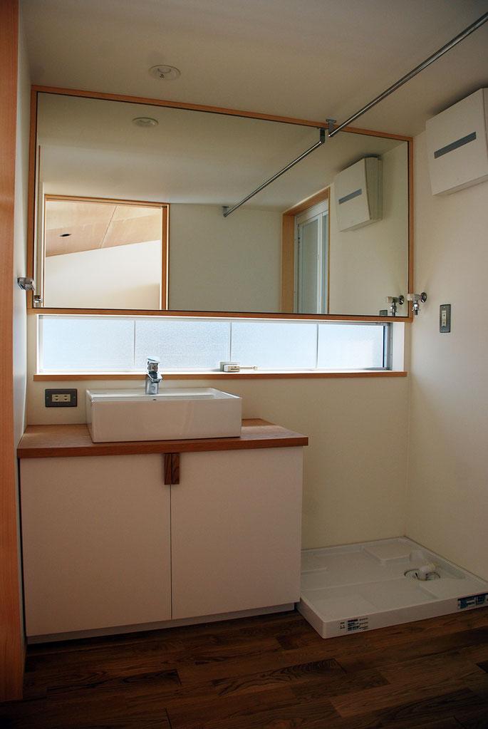 脱衣室正面は鏡張りとして、狭い空間ながらも広がりが感じられるようにしている。