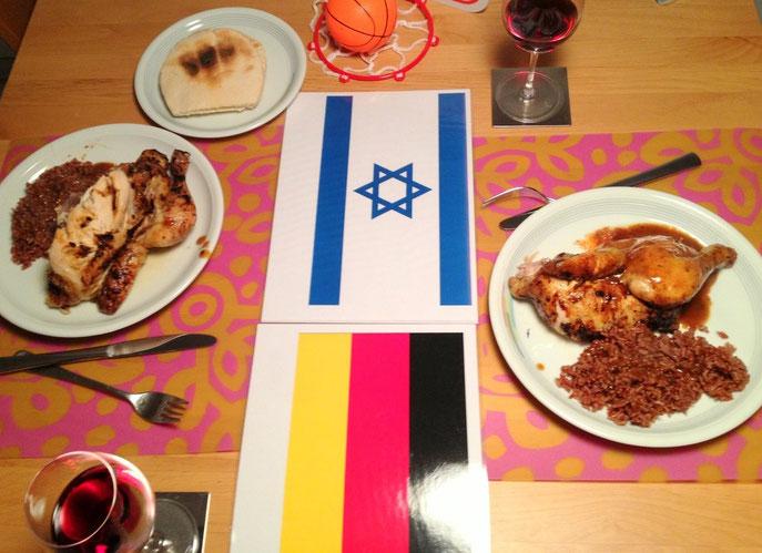Zwei Teller mit einem Hähnchengericht mit Reis auf israelischer und deutscher Flagge