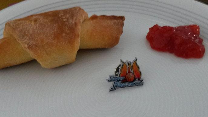 Frühstückskipferl mit Marmelade und einem Pin von Phoenix Hagen auf einem Teller