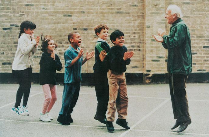 Dieses Bild wurde im Times Newspaper veröffentlicht und zeigt Yehudi Menuhin und Kinder auf einem Schulhof. Der Jahrhundertgeiger befindet sich vor einer Gruppe von fünf Kindern. Er klatscht in die Hände und alle springen freudeschreiend in die Luft.