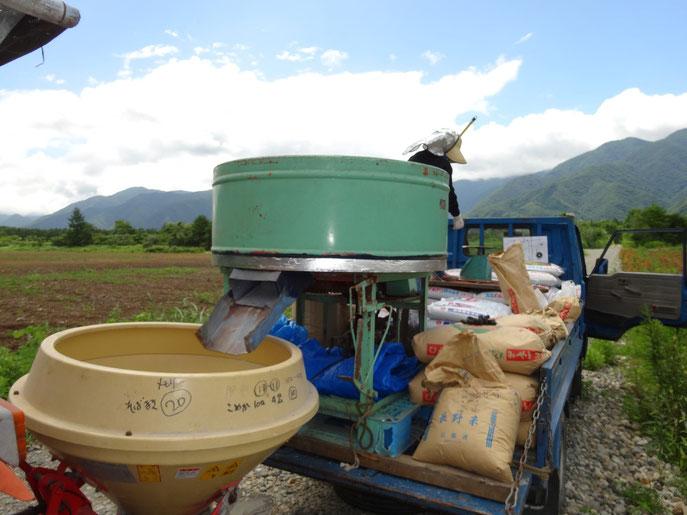肥料と種をトラックの荷台で混ぜる