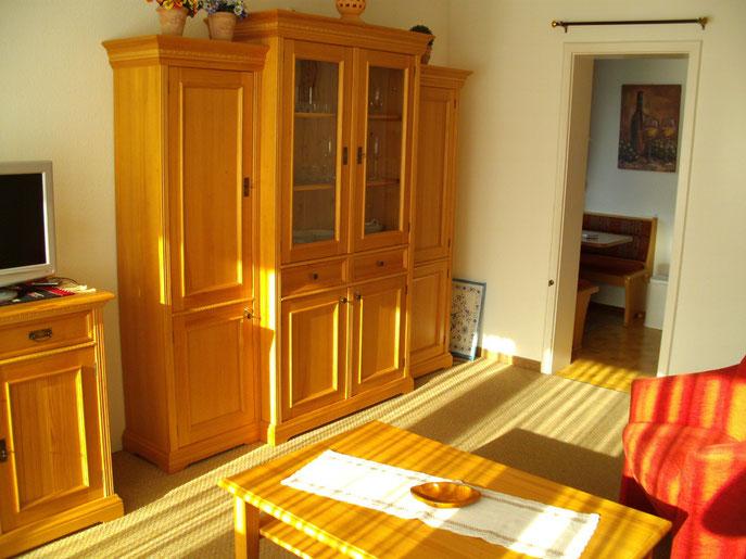 Moderne Einrichtung der Ferienwohnung Grünten, die Sonne scheint dabei in die Fewo Grünten und der Blick wandert nach hinten in die direkt angrenzende Küche