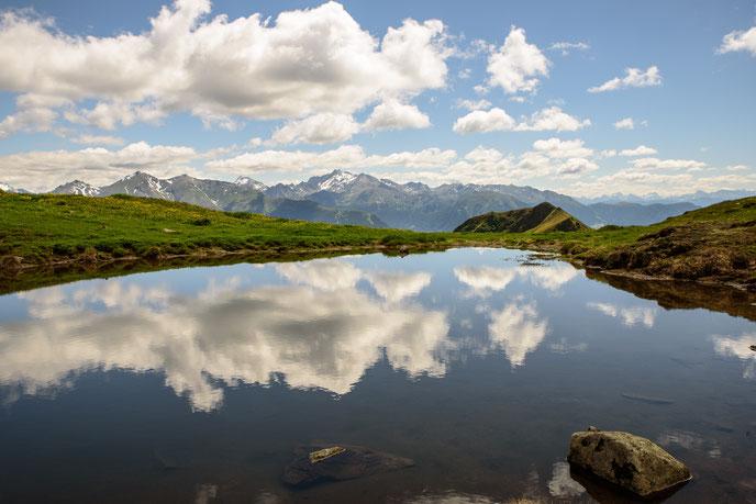Klarer Bergsee mit Spiegelung der Wolken