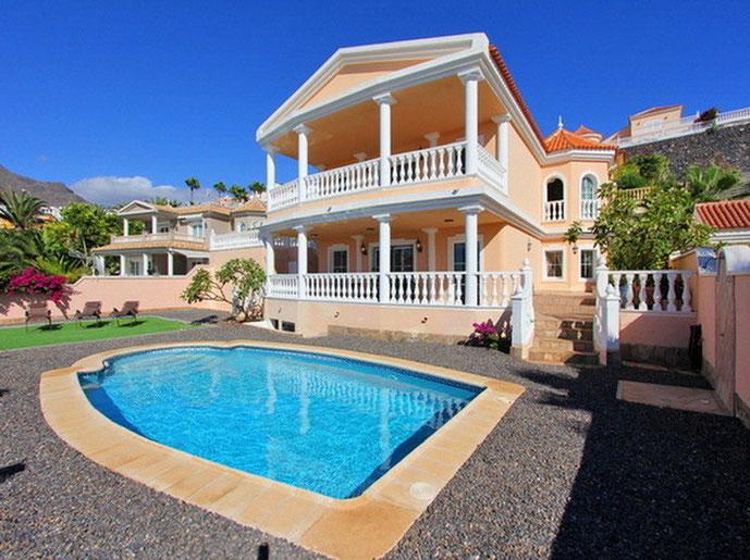 Sicht vom elegant geschwungen Pool auf die Villa mit Säulen, die die Terrassen der Villa tragen.