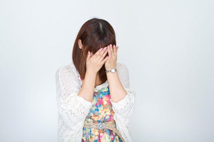手で顔を覆う女性