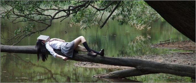 木の上で寝る女性