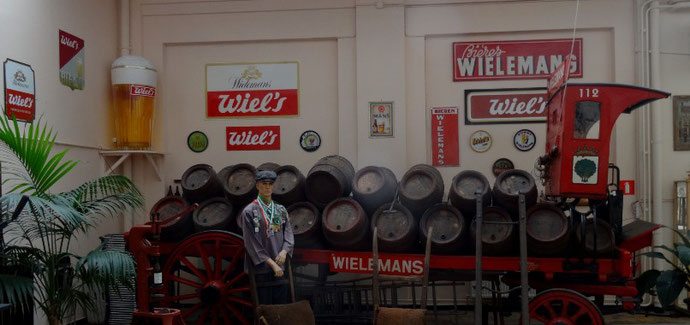 Photo: Le vieux camion rouge de Wielemans chargé de tonneaux devant un décor mural fait de panneaux publicitaires Wiels et Wielemans et d'un énorme verre de bière en hauteur dans le coin. Devant le camion, le mannequin d'un livreur.