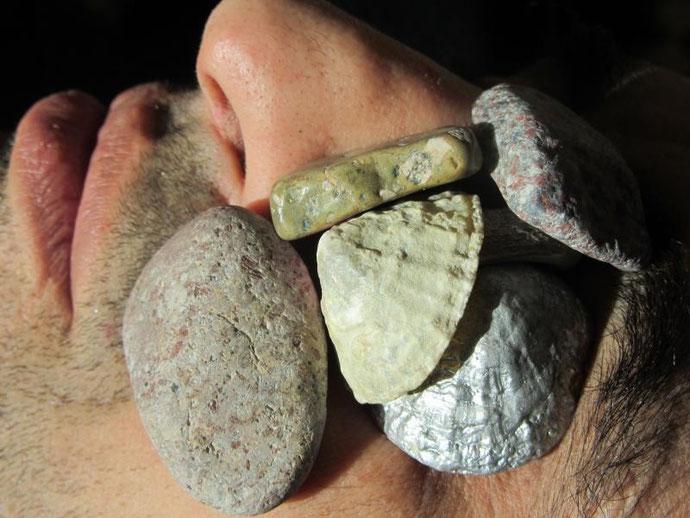 Gros plan sur le visage d'un homme d'on les yeux sont recouverts de pierres