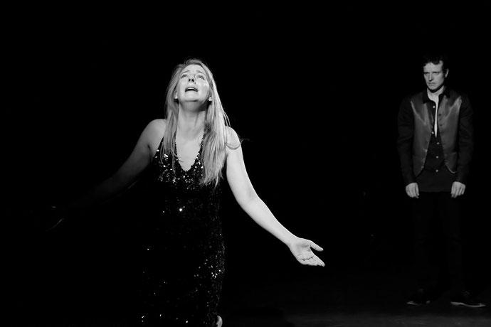 Deux acteurs de la pièce sur scène : une femme pleurant et dans son dos un homme