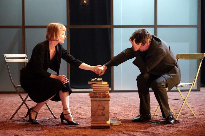 Photo de 2 acteurs de la pièce se tenant la main sur scène