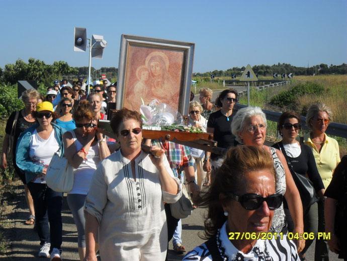 Pina è alla destra di chi guarda, con capelli bianchi e occhiali da vista. Assieme alla sorella Tina porta a spalla il quadro della Madonna di Jaddico.