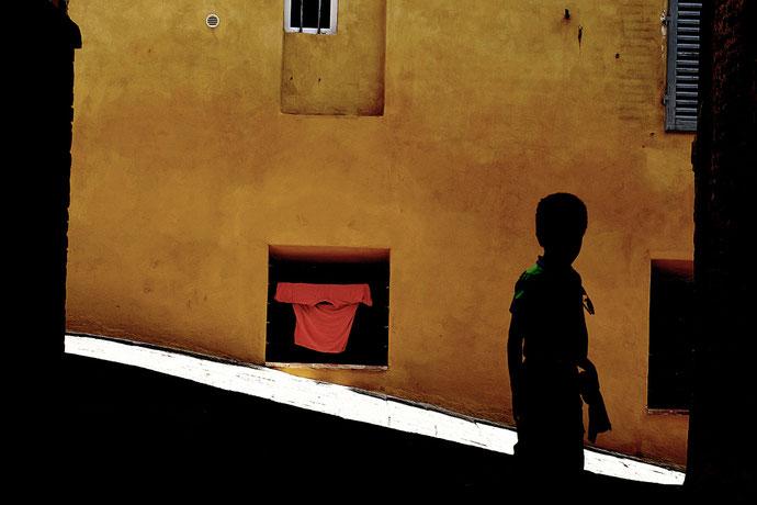Mathieu Guillochon photographe, street Photo, photographie, Sienne, Toscane, Italie, terre de Sienne, jaune, orange, couleurs, enfant, ombre, t-Shirt, rue, vieille ville, été, lumière.