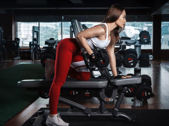 Auf dem Bild ist eine Frau im Fitnesstudio von der Seite zu sehen. Sie macht einseitige Ruderzugbewegungen mit der Kurzhantel.
