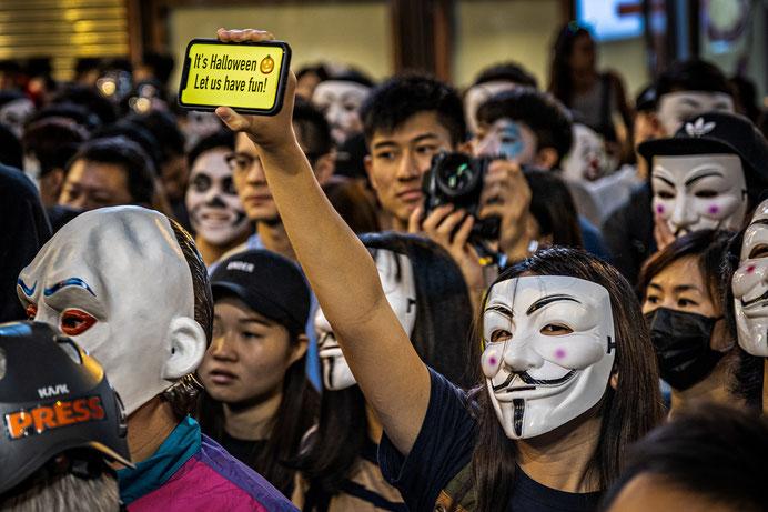 笑みを浮かべる「ガイ・フォークス(Guy Fawkes)」の仮面を着用するデモ抗議者たち。