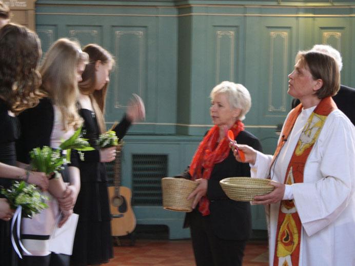 Unsere Küsterin Kristiane Nitzsche und Pastorin Dagmar Rosenberg überreichen den frisch Konfirmierten kleineGeschenke.