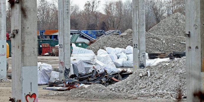 """Weiße Säcke auf dem Gelände. Aufschrift: """"Mineralfaserabfälle. Inhalt kann krebserregenden Feinstaub freisetzen"""".    Foto: hbz/Michael Bahr"""