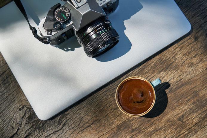 Cette photo représente un appareil photo devant une tasse de café une idée pour découvrir mes cours de photographie