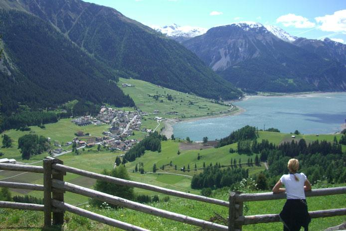 Ausblick Richtung Reschen am Reschenpass im Vinschgau: tief blau der Reschensee mit dem versunkenen Dorf Reschen