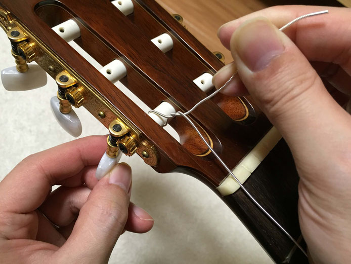 弦の交換(クラシックギターの弦の張り方)9. 手で弦を押さえながらペグを回す
