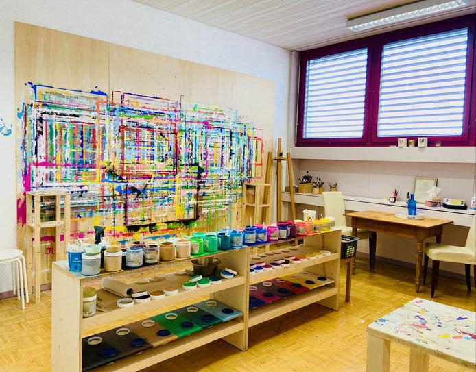 Atelier mit farbigen Wänden und Gestell mit Farben und Pinsel